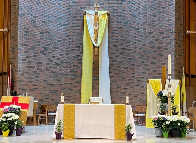 St. Mary's altar area at Easter decorated with flowers and yellow and white banners