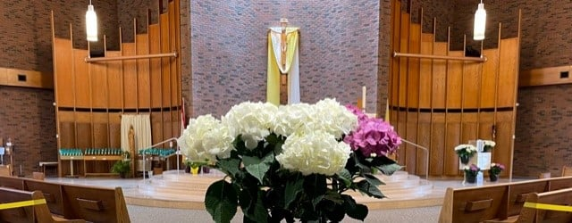 St. Mary's altar area at Easter decorated with flowers and yellow and white banners with flowers in the forefront